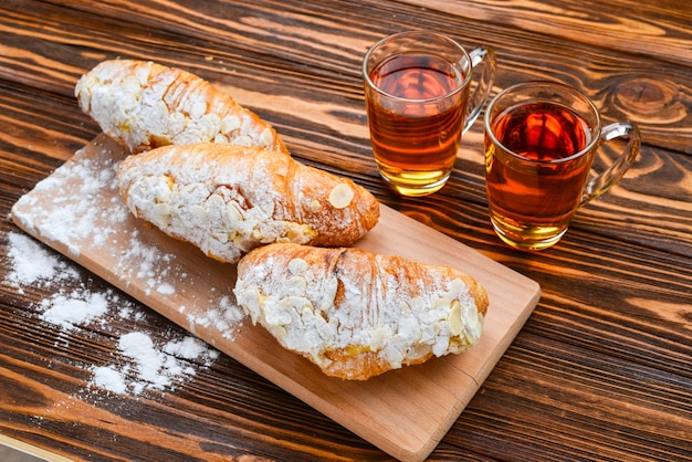 Croissants with almonds and tea on a wooden table.