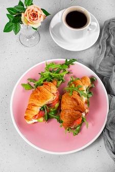 Arugula, 아보카도 및 연어, 블랙 커피 한 잔과 테이블에 오렌지 주스 한 잔, 아침 식사 개념 세로 사진 크로와상.