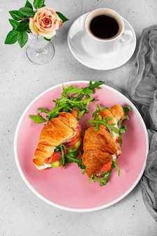 Croissants with arugula, avocado and salmon, a cup of black coffee and a glass of orange juice on the table, breakfast concept vertical photo.