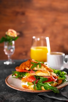 Croissants with arugula, avocado and salmon, a cup of black coffee and a glass of orange juice on the table
