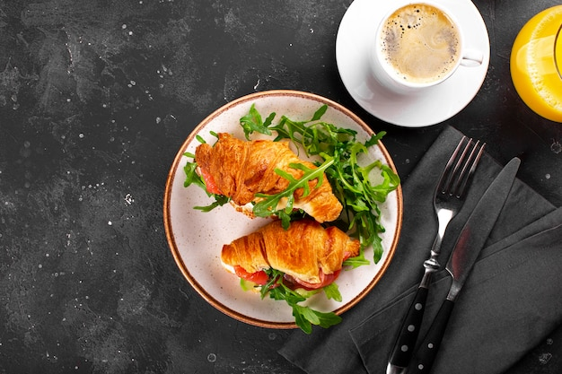Croissants with arugula, avocado and salmon, a cup of black coffee and a glass of orange juice