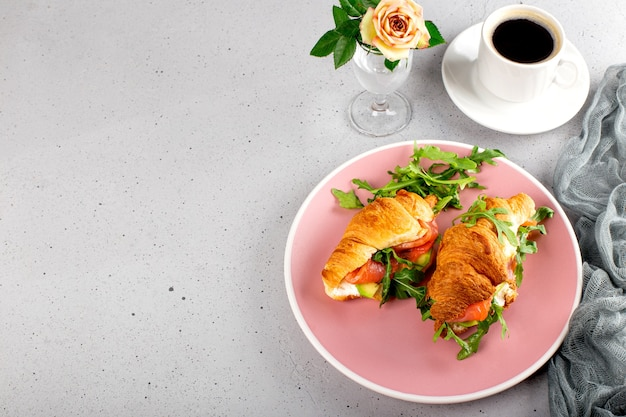 Croissants with arugula, avocado and salmon and a cup of black coffee