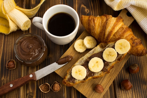 木製のまな板にチョコレートクリームとバナナのクロワッサン。上からの眺め。
