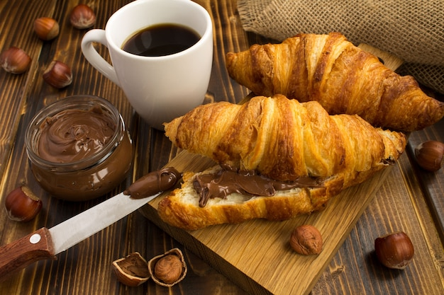 Croissants with chocolate cream and coffee on the rustic wooden background