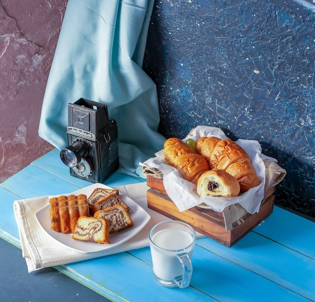 Croissants with chocolate cream, vanilla pie and a glass of milk.