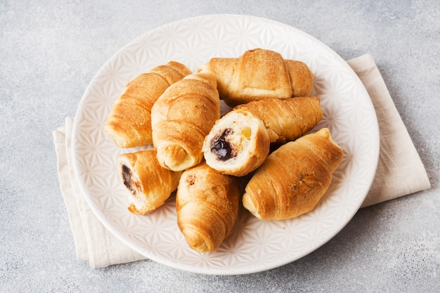 Croissants with chocolate filling on a plate gray background.