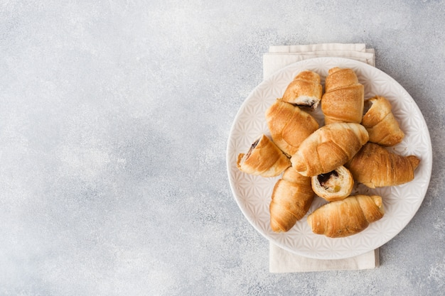 Croissants with chocolate filling on a plate gray surface