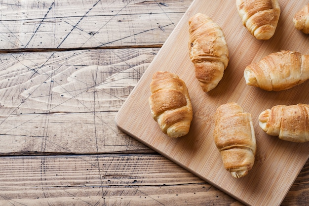 Croissants with chocolate filling on wooden background.