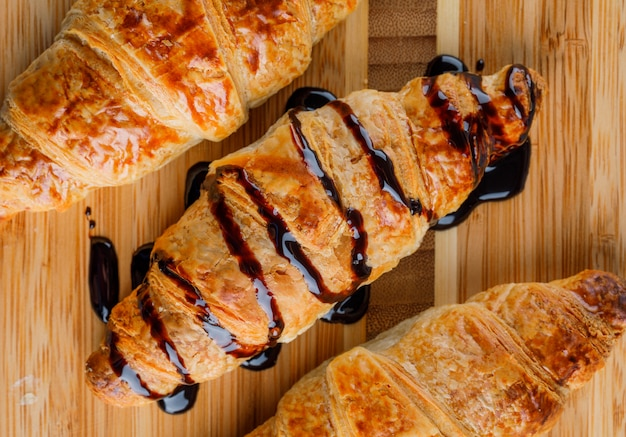 Croissants with chocolate sauce on wooden table, close-up.