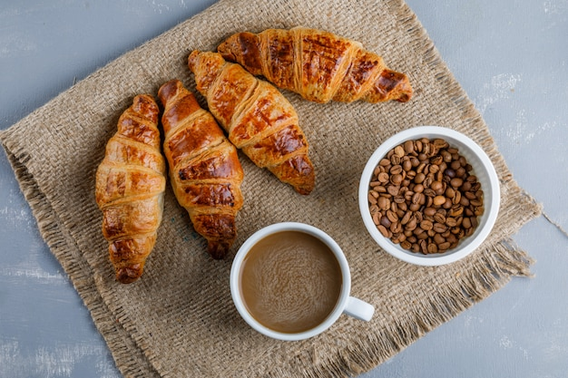 Croissants with coffee and beans on plaster and piece of sack, flat lay.