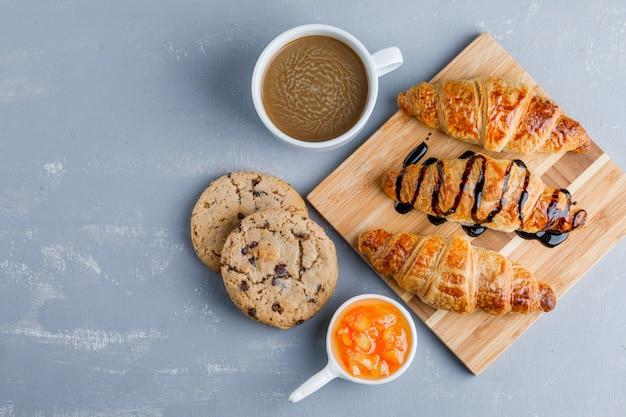 Круассаны с кофе, печеньем, соусом на плоской подложке и деревянной доске