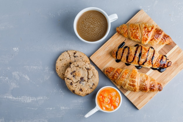 Croissants with coffee, cookies, sauce flat lay on plaster and wooden board