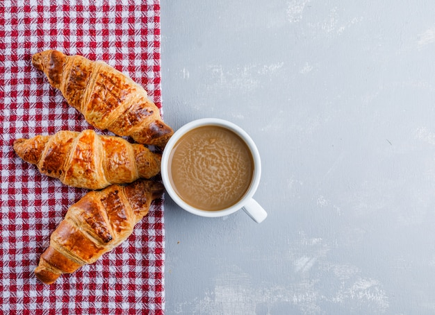 Croissants with coffee on plaster and picnic cloth, flat lay.