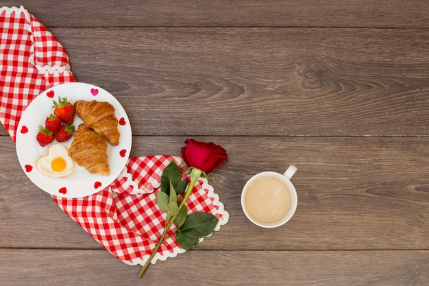 Croissants with coffee and red rose