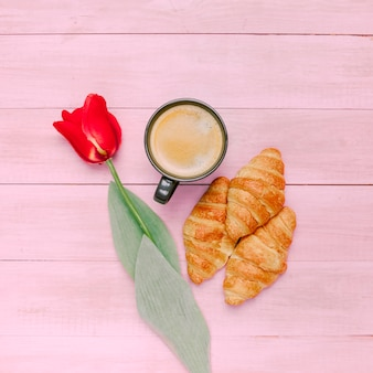 Croissants with coffee and tulip on table