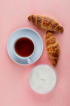 クリームチーズとクロワッサン、ピンクのテーブルでお茶のトップビュー