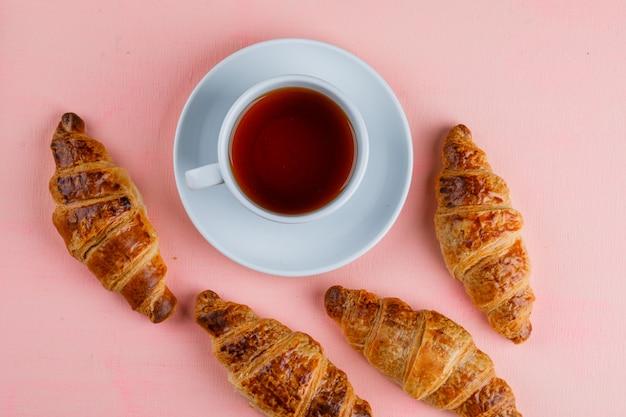 Круассаны с чашкой чая лежат на розовом столе