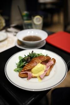 Круассаны с яйцами бенедикт и ветчиной выглядят аппетитно на белом блюде в ресторане.