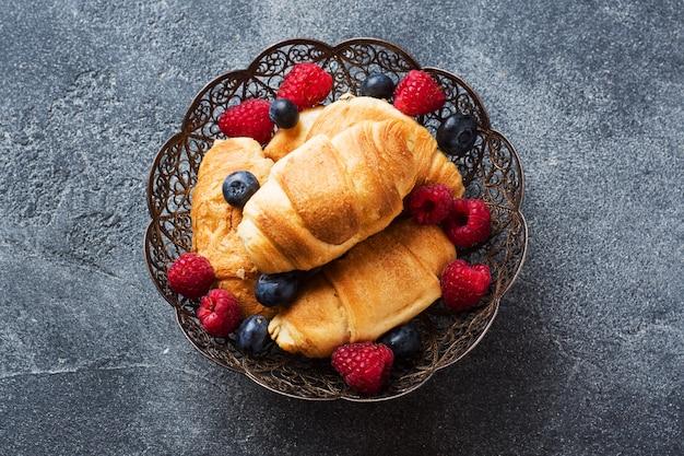 暗いコンクリート背景に新鮮なラズベリーとブルーベリーのクロワッサン。コピースペース。朝食のコーヒー蜂蜜の概念。
