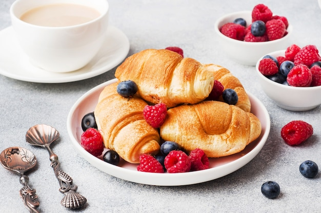 Croissants with fresh raspberries and blueberries on grey concrete background. copy space. concept of breakfast coffee honey