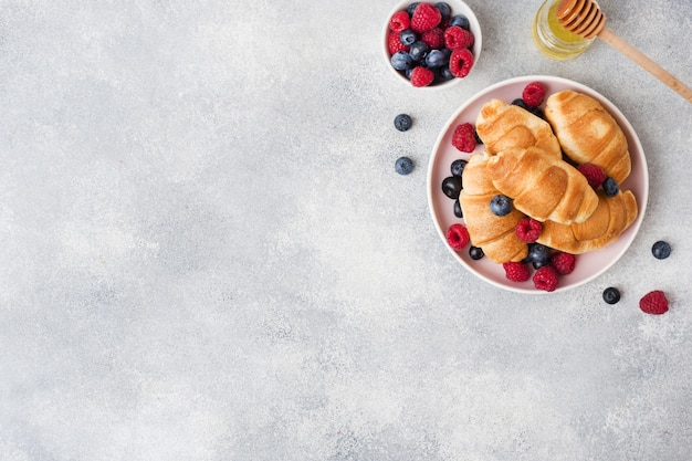Croissants with fresh raspberries and blueberries on grey concrete surface