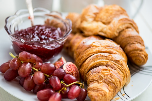 Croissants with icing, cup of tea, grapes, sugar and strawberry jam