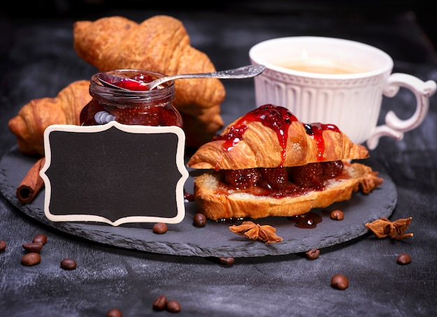 Croissants with raspberry jam and black empty wooden plaque