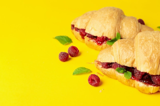 Croissants with raspberry jam on yellow background