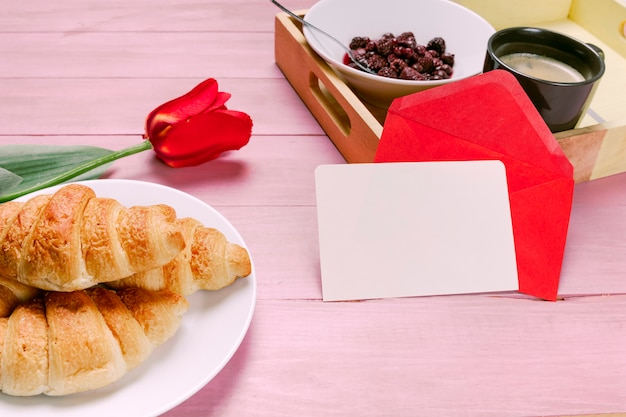 Croissants with red tulip and blank paper