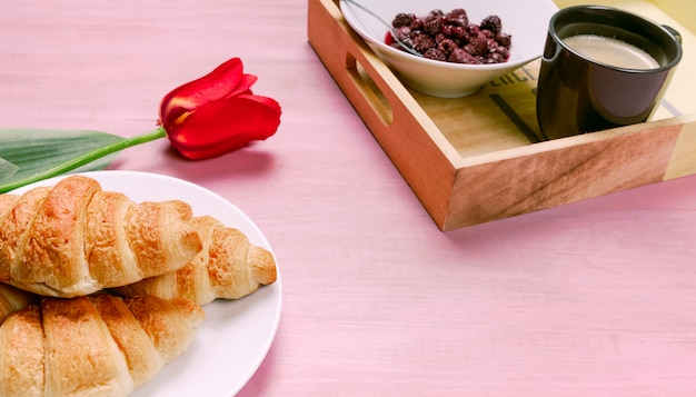 Croissants with red tulip and tray with berries