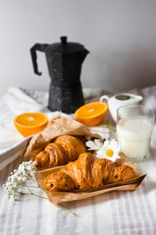 Croissants with sliced oranges and milk