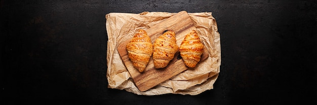Croissants on wooden board placed over crumpled baking paper. old rustic background. banner shape.