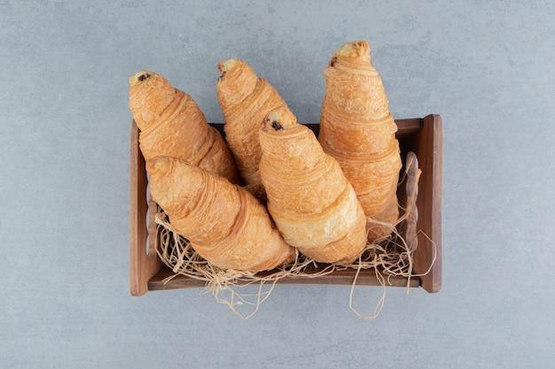 Croissant in ciotola di legno sullo sfondo di marmo. foto di alta qualità