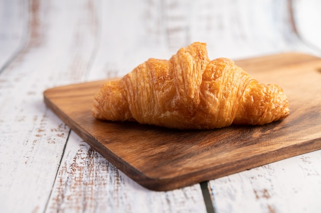 Croissants on a wooden cutting board.