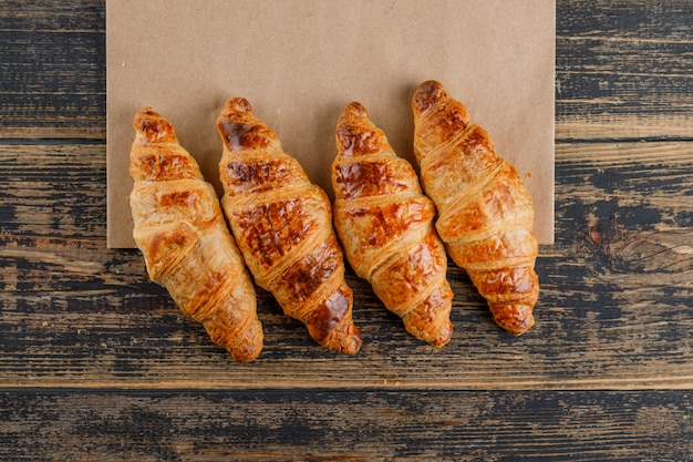 Croissants on wooden and paper bag, flat lay.