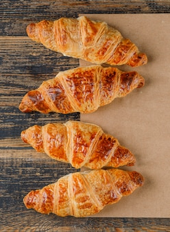 Croissants on wooden and paper bag. flat lay.