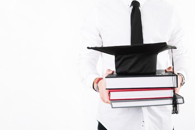 Выпускник урожая с книгами и кепкой