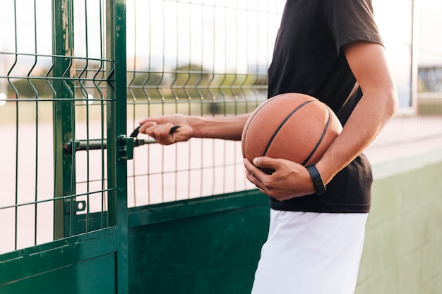 Crop anonymous athlete male opening basketball court