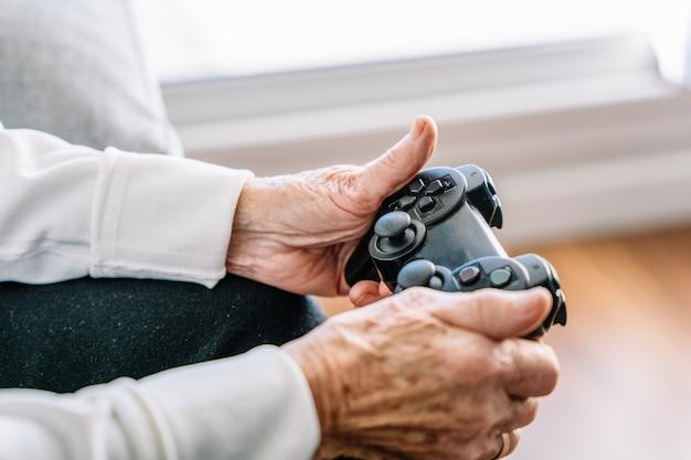 집에서 비디오 게임을하는 익명의 오래된 seniour 여성 자르기