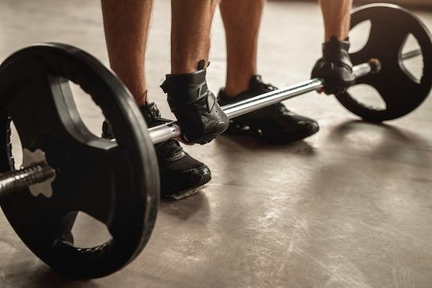 ジムでのウエイトトレーニング中に重いバーベルを持ち上げる準備をしながら、手袋をはめて匿名のスポーツマンを前に曲げる
