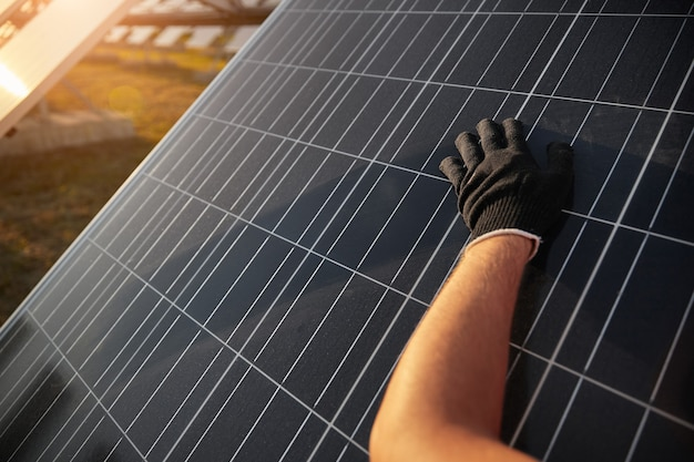 Урожай анонимного рабочего в черной перчатке, протирающего пыльную фотоэлектрическую панель во время ремонтных работ на солнечной электростанции