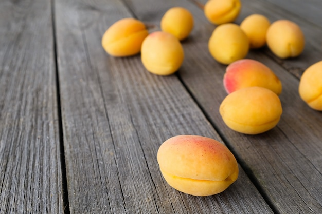 The crop of apricots on a dark wooden floor