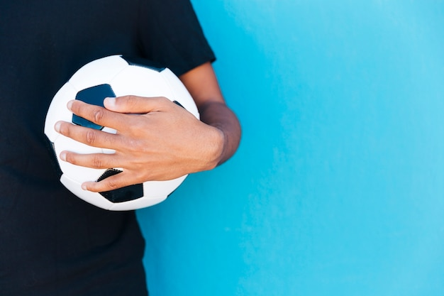 Crop of arm holding soccer ball near wall