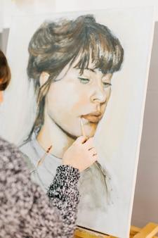 Crop artist painting portrait