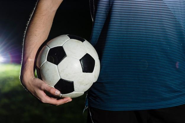 Crop athlete holding soccer ball