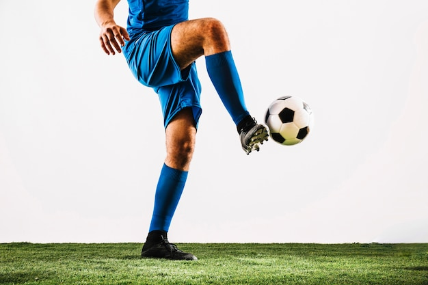Crop athlete juggling soccer ball