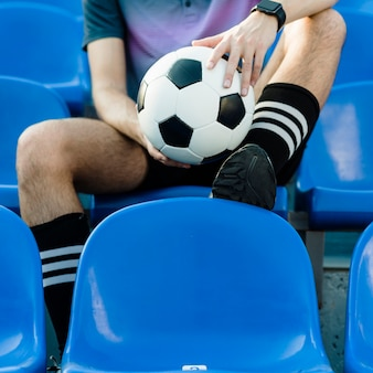 Atleta del raccolto con pallone da calcio sullo stadio