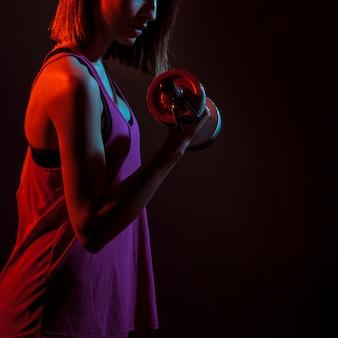 Crop athletic woman training bicep in dark