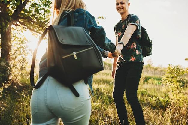 幸せなハンサムな男性の手を握って、木と太陽に照らされた緑の草の上に立って彼を導くジーンズの夏服の女性の背面図