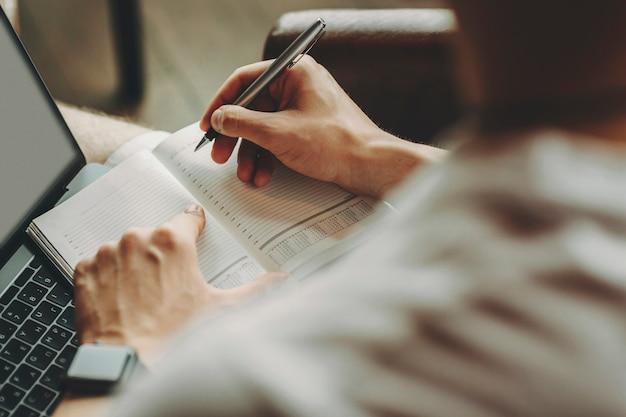 ノートパソコンで座っているデイリープランナーのページにペンと人差し指を保持しているライトシャツの男性の背面図をトリミングします。